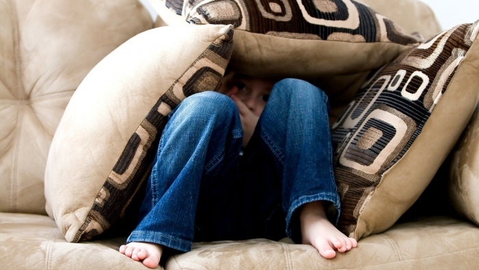 Image of child hiding under pillows
